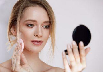 girl applies powder foundation make up
