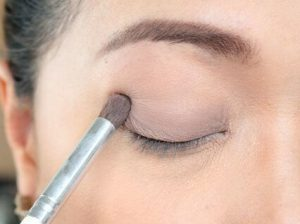 girl applies eyeshadow primer with a brush on her eye lid