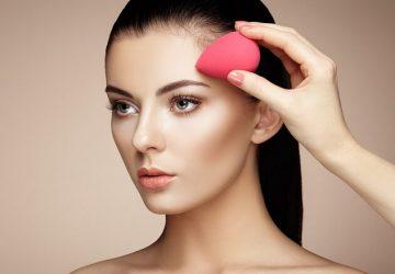 girl applies foundation with beauty blender sponge