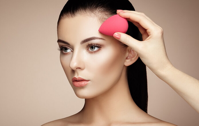 girl applies foundation with beauty blender sponge