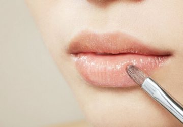 girl applies lip balm on lips with a brush
