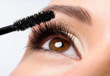 girl applies black mascara on her lashes