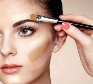 concealer application on a face with brush