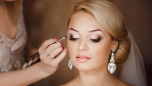 makeup artist makes wedding makeup to a bride