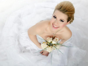 smiling bride with trendy makeup holding flowers