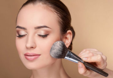 girl applies loose powder on face with a kabuki brush